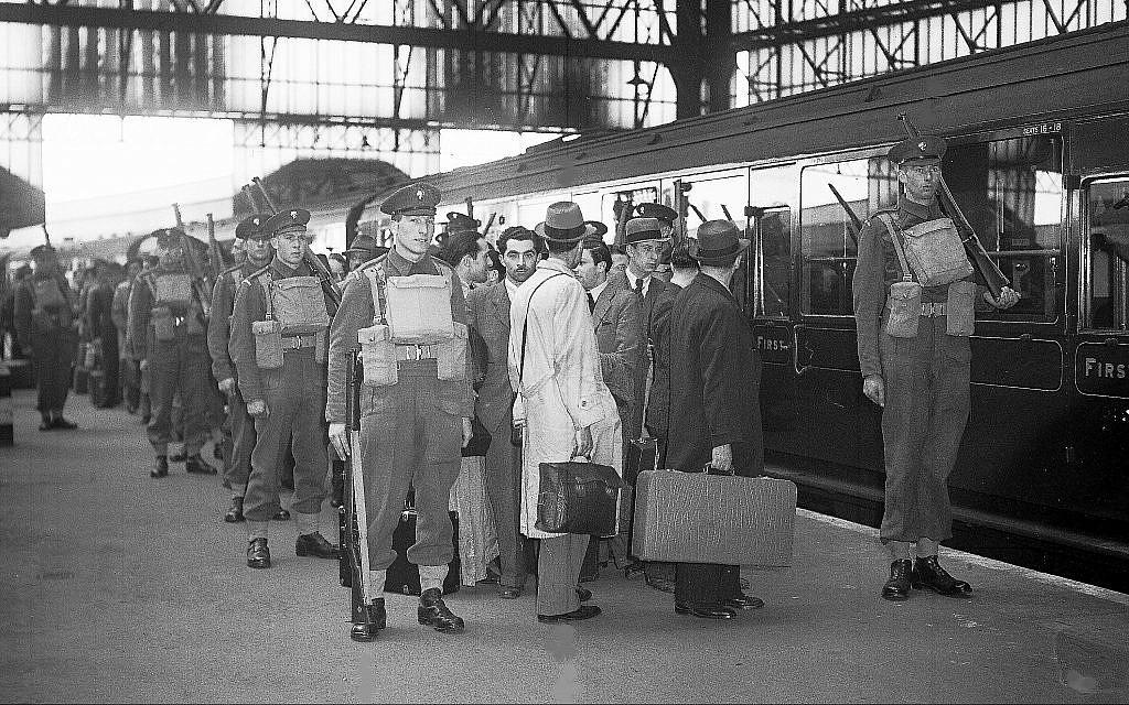 Des étrangers ennemis, arrêtés lors d'une grande rafle policière, quittent Londres, en Angleterre, le 17 mai 1940, sous une lourde escorte militaire pour des camps d'internement. (AP Photo)