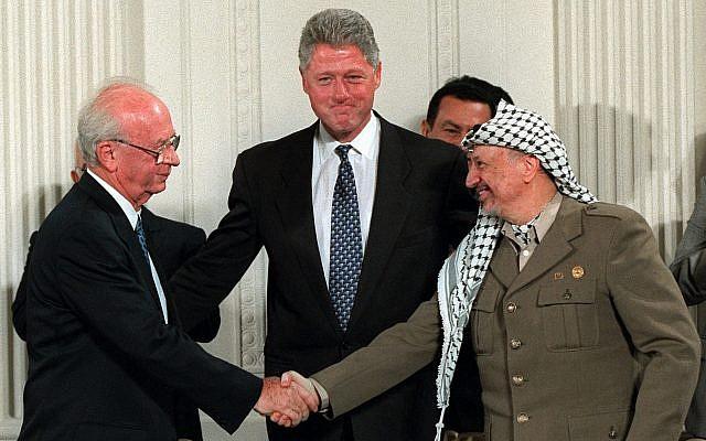 Le président Clinton invite le Premier ministre israélien Yitzhak Rabin, (gauche) et le chef de l'OLP Yasser Arafat à se serrer la main dans la Chambre Est de la Maison Blanche, le jeudi 28 septembre 1995. Le président égyptien Hosni Mubarak est derrière Arafat. (AP Photo/Doug Mills)