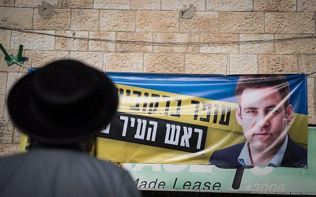 Un homme ultra-orthodoxe se tient devant le siège de campagne du candidat à la mairie de Jérusalem, Ofer Berkovitch, à Jérusalem, le 8 novembre 2018, avant le second tour des élections municipales qui ont lieu le 13 novembre. (Crédit : Hadas Parush/Flash90)