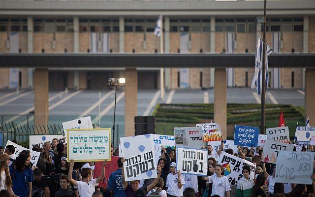 Des jeunes Israéliens tiennent des pancartes alors qu'ils protestent devant la Knesset pour réclamer une solution aux cerfs-volants incendiaires et aux roquettes lancées depuis la bande de Gaza sur les villes israéliennes, après avoir marché du sud du pays jusqu'à Jérusalem le 8 novembre 2018. (Crédit : Yonatan Sindel / Flash90)