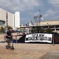 """Des Israéliens regardent une structure ressemblant à un sous-marin avec une pancarte disant """"Avec Bibi [Netanyahu], le pays est en train de couler"""", sur la place Habima de Tel Aviv, le 10 novembre 2018 (Crédit : Miriam Alster/Flash90)"""
