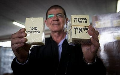 Un homme montre les bulletins de vote des candidats à la mairie de Jérusalem Ofer Berkovich et Moshe Lion, pendant les préparations pour le second tour dans un entrepôt de Jérusalem, le 11 novembre 2018 (Crédit : Yonatan Sindel/Flash90)