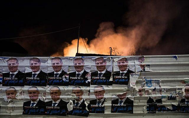 Des affiches de campagne électorale devant la fumée émanant d'un bâtiment incendié par une roquette de la bande de Gaza dans le sud d'Israël, à Sdérot, le 12 novembre 2018 (Crédit : Hadas Parush/Flash90)