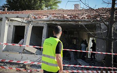 Des personnes se rassemblent devant une maison touchée par une roquette tirée depuis la bande de Gaza dans la ville d'Ashkelon, dans le sud d'Israël, le 13 novembre 2018 (Crédit : Hadas Parush / Flash90).
