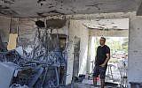 Un homme constate les dégât dans un immeuble d'Ashkelon frappé par une roquette du Hamas, le 13 novembre 2018. (Crédit : Nati Shohat/Flash90)
