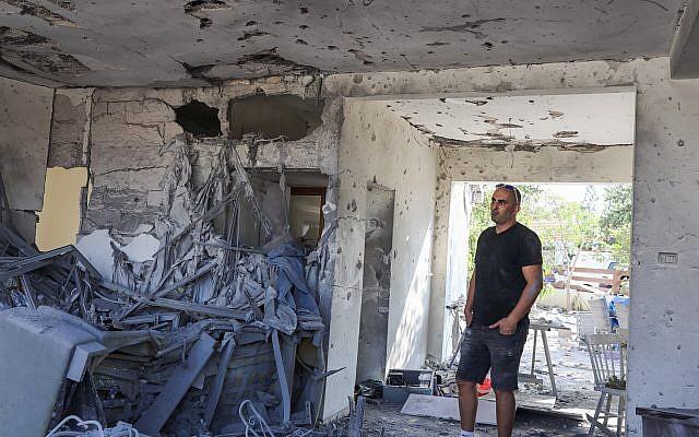 Un homme debout à l'intérieur d'une maison qui a été touchée par une roquette tirée depuis la bande de Gaza dans la ville d'Ashkelon, au sud d'Israël, le 13 novembre 2018 (Crédit : Nati Shohat/Flash90)