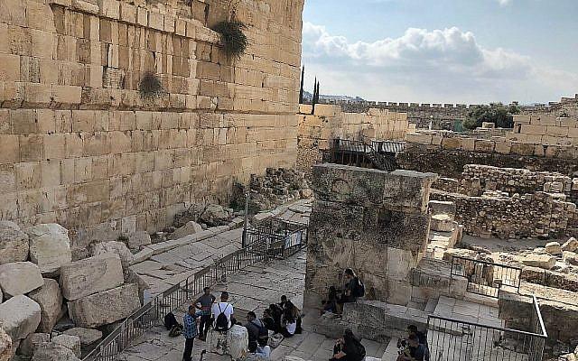 """La pierre servant d'unité de mesure du poids dans la Bible """"Beka"""" a été découverte dans de la terre provenant de fouilles archéologiques menées en 2013 sur les fondations du Mur occidental dans un fossé de drainage (photo du 17 octobre 2017 en bas à gauche) directement sous l'Arche de Robinson. (Amanda Borschel-Dan/Times of Israel)"""