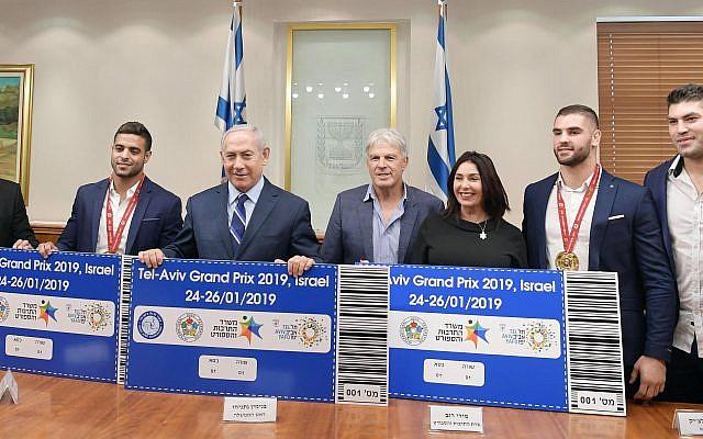 Le Premier ministre Benjamen Netanyahu et la ministre de la Culture et des Sports Miri Regev, entourés par l'équipe de judo israélienne présentent les futurs tickets pour le Grand Prix 2019 de Tel Aviv. (Crédit photo: GPO)