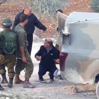 Le 11 novembre 2018, le colonel Ahmed Abu al-Rub, chef de la police de l'Autorité palestinienne à Hébron, aide les soldats israéliens à remplacer un pneu d'un véhicule militaire. (Crédit : capture d'écran Twitter)