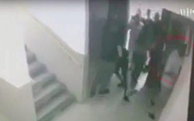 Des inspecteurs de police interpellent un lycéen israélien d'origine éthiopienne à Ashdod, sous le regard du directeur de l'école. (Crédit : Kan)