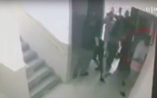 Des détectives de la police interpellent un lycéen israélien d'origine éthiopienne à Ashdod, sous le regard du directeur d'école. (Crédit : Kan)