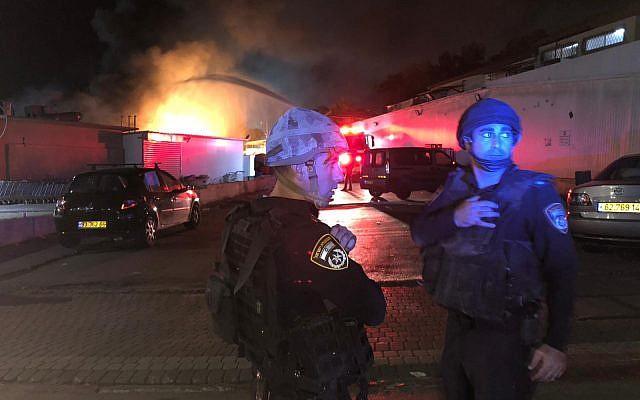 Des policiers se tiennent près d'un incendie d'un immeuble à Sdérot le 12 novembre 2018. (Crédit : Police israélienne)