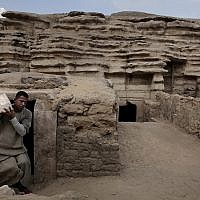 Un employé porte  une statue retrouvée dans une tombe des pyramides de  Saqqara, le 10 novembre 2018. (Crédit : Nariman El-Mofty/AP)