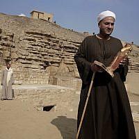 Le directeur des fouilles tient une statue retrouvée dans une tombe des pyramides de  Saqqara, le 10 novembre 2018. (Crédit : Nariman El-Mofty/AP)