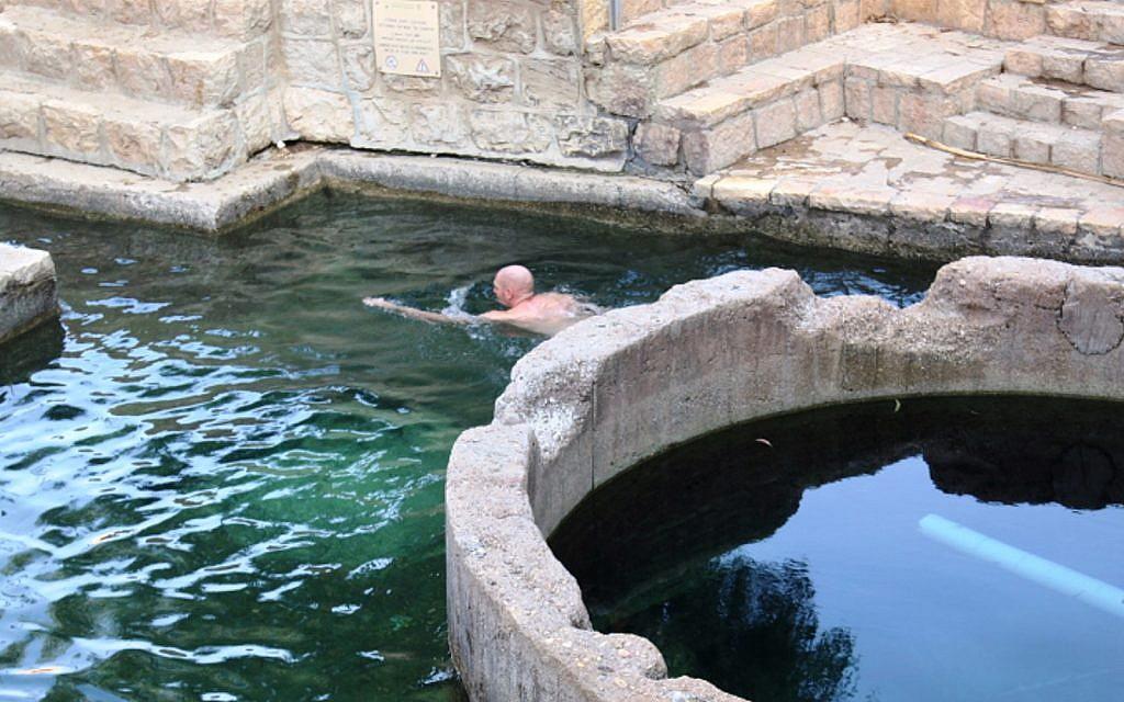 Un visiteur se baigne dans le bassin d'Ein Fawwar, dans les collines de Judée (Crédit : Shmuel Bar-Am)