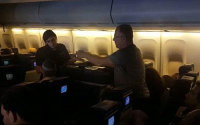 Une hôtesse sert un passager sur un vol El Al en provenance de New York et en direction d'Israël le 18 novembre 2018 (Capture d'écran : Israel Hayom)