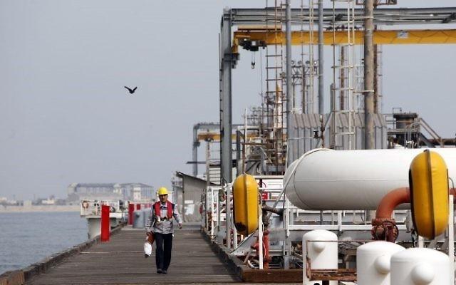 Cette photo du 12 mars 2017 montre un ouvrier iranien marchant sur la plate-forme de l'installation pétrolière de l'île de Khark, sur la côte du Golfe. (Crédit : AFP / Atta Kenar)