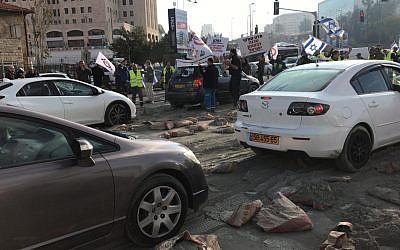 Les employés de l'usine Hartuv déversent des sacs de ciment à l'entrée de Jérusalem, bloquant la route de la ville, le 25 novembre 2018 (Crédit : Unité du porte-parole de la police israélienne)