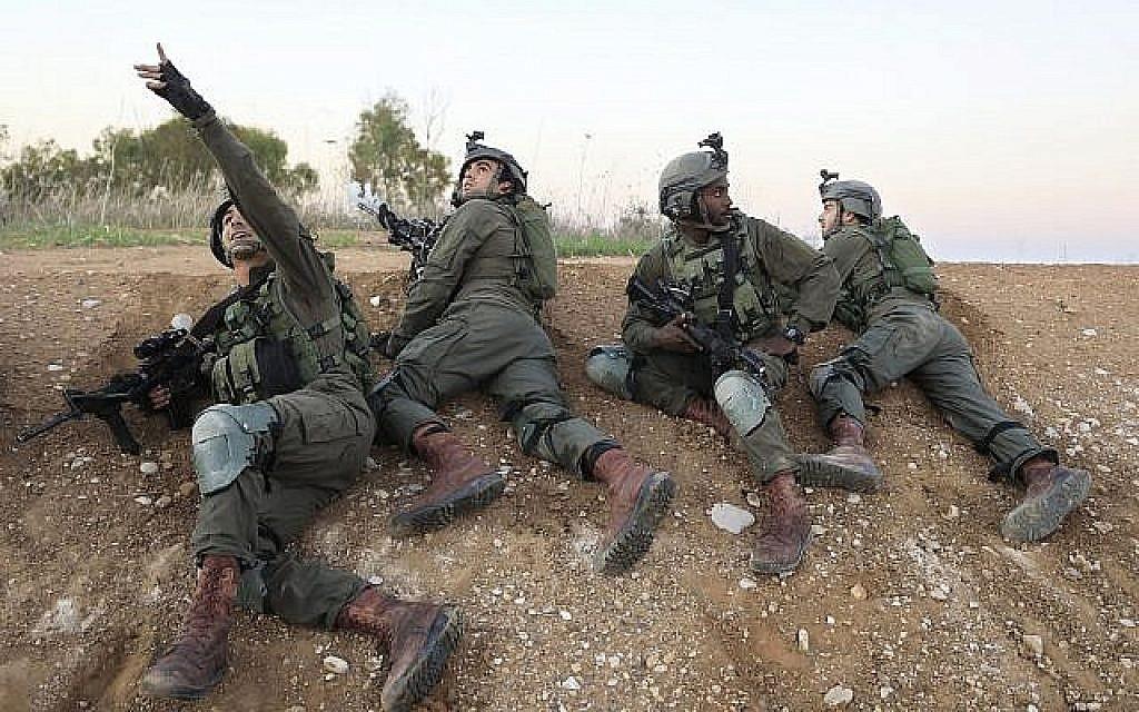 Des soldats israéliens se mettent à l'abri près de la frontière entre Israël et Gaza, le 12 novembre 2018. (Crédit : AP / Tsafrir Abayov)