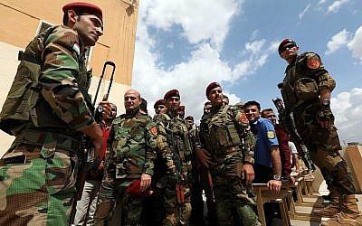 Des membres kurdes irakiens de la sécurité font la queue devant un bureau de vote pour les élections législatives du 10 mai 2018 à Arbil, capitale de la région autonome kurde du nord de l'Irak. (AFP Photo/Safin Hamed)