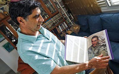 Simha Goldin, le père du soldat israélien Hadar Goldin, montre une photo de son fils lors d'une interview au domicile familial dans la ville de Kfar Saba, dans le centre d'Israël, le 29 août 2018. (AFP Photo/Jack Guez)