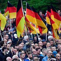 """Illustration : Des manifestants brandissent des drapeaux allemands à un rassemblement du mouvement de droite """"Pro Chemnitz"""", du parti d'extrême-droite AfD et du parti anti-islam Pegida à Chemnitz, le 1 septembre 2018. (Crédit : AFP PHOTO / John MACDOUGALL)"""