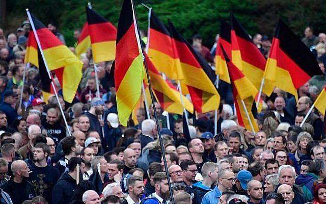 """Des manifestants brandissent des drapeaux allemands à un rassemblement du mouvement de droite """"Pro Chemnitz"""", du parti d'extrême-droite AfD et du parti anti-islam Pegida à Chemnitz, le 1 septembre 2018. (Crédit : AFP PHOTO / John MACDOUGALL)"""
