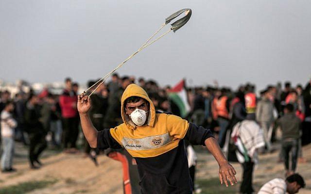 Un Palestinien lance une pierre vers les forces israéliennes pendant des affrontements sur la frontière avec la bande de Gaza, le 30 novembre 2018 (Crédit :  MAHMUD HAMS / AFP)