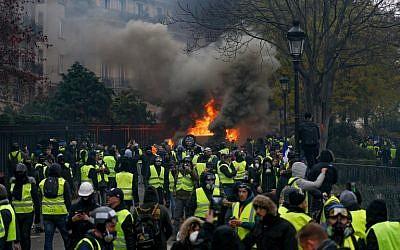 Des manifestants se rassemblent autour d'une voiture en feu lors d'une manifestation des Gilets jaunes contre la hausse du prix du pétrole et du coût de la vie, le 1er décembre 2018 à Paris. (Geoffroy VAN DER HASSELT / AFP)