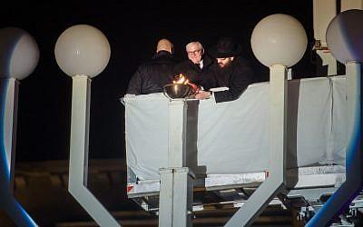 Le président allemand Frank-Walter Steinmeier, au centre, et le rabbin  Yehuda Teichtal, à droite, allument un candélabre devant la porte de Brandenburg à Berlin, le 2 décembre 2018 (Crédit :  Gregor Fischer / dpa / AFP)