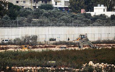 Des soldats israéliens devant une machine d'excavation près de Metula, à la frontière avec le Liban, le 4 décembre 2018. (Crédit : JALAA MAREY / AFP)