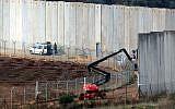 Des Israéliens travaillent près du mur frontalier en béton séparant les deux pays,  une photo prise au sud du village libanais de Kfar Kila, à la frontière avec Israël, le 9 décembre 2018 (Crédit :  Ali DIA / AFP)