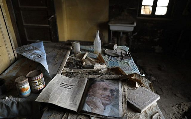 Une copie d'un magazine avec le portrait du général israélien Moshe Dayan, sur la table d'une église étiopienne de Qasr al-Yahud, fermée depuis 50 ans. (Crédit : MENAHEM KAHANA / AFP)