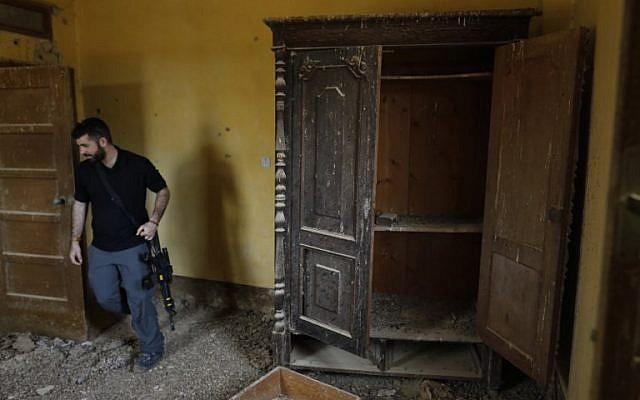 Un agent de sécurité israélien inspecte l'intérieur d'une église éthiopienne  à Qasr al- Yahud, en Cisjordanie, le 9 décembre 2018. (Crédit : MENAHEM KAHANA / AFP)