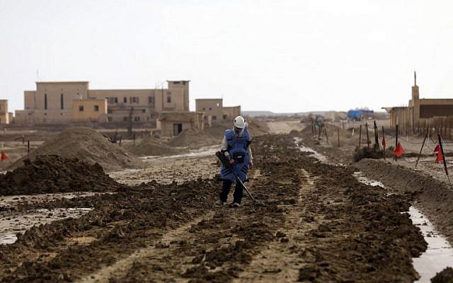 Un employé du ministère de la Défense utilise un détecteur de métaux pour vérifier la présence de mines à Qasr al- Yahud, en Cisjordanie, le 9 décembre 2018. (Crédit : MENAHEM KAHANA / AFP)