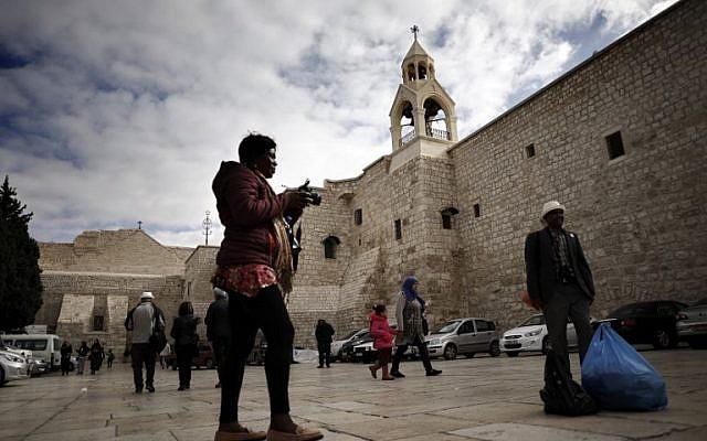 Touristes et pèlerins chrétiens se photographient devant l'Eglise de la Nativité en Cisjordanie, le 12 décembre 2018. (Crédit : THOMAS COEX / AFP)