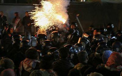 La police anti-émeutes lance des gaz lacrymogènes lors d'une manifestation contre la décision du gouvernement d'élever les impôts dans la capitale d'Amman, en Cisjordanie, le 13 décembre 2018 (Crédit :  Khalil MAZRAAWI / AFP)