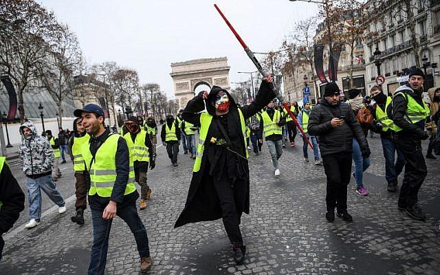 Un homme porte un masque d'Anonymous et un sabre laser de Jedi de Star wars durant les manifestations de gilets jaunes devant l'Arc de Triomphe à Paris, le 15 décembre 2018. (Crédit : Christophe Archambault/AFP)