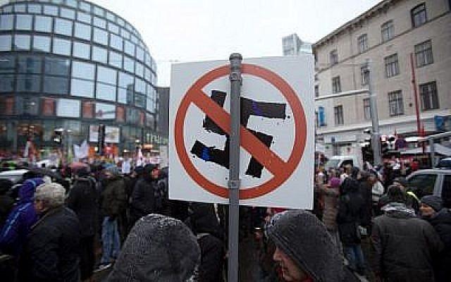 Les manifestants brandissent une pancarte avec une croix gammée barrée lors d'un rassemblement organisé au premier anniversaire de la coalition gouvernementale formée entre les conservateurs et le parti de la Liberté d'extrême droite, le 15 décembre 2018 (Crédit :  ALEX HALADA / AFP)