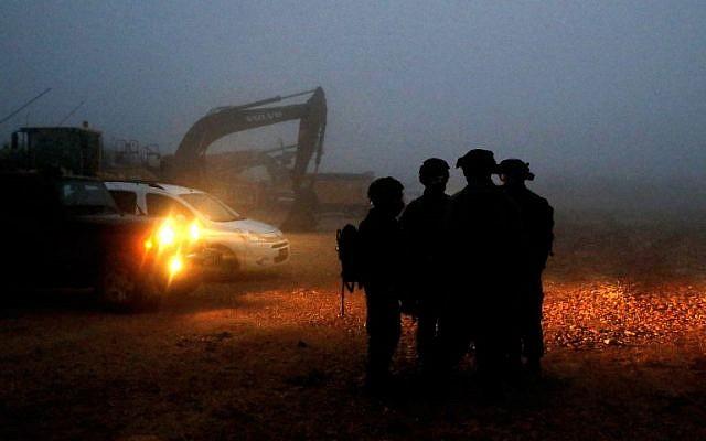 Des soldats israéliens se dirigent vers des engins de chantier utilisés pour localiser les tunnels d'attaque du Hezbollah le long de la frontière avec le Liban, près de la ville de Metula, au nord d'Israël, le 19 décembre 2018. (Jack Guez/AFP)