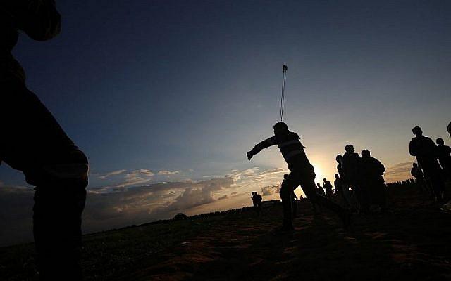 Un Palestinien utilise une fronde pour jeter des pierres pendant des émeutes près de la frontière avec Israël, à Khan Younès, dans le sud de la bande de Gaza, le 21 décembre 2018 (Crédit : Said Khatib/AFP)