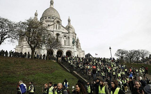 Certains manifestants des gilets jaunes réunis sur la colline de Montmartre, à Paris, devant la basilique du Sacré-Coeur, le 22 décembre 2018 (Crédit :  Sameer Al-Doumy / AFP)