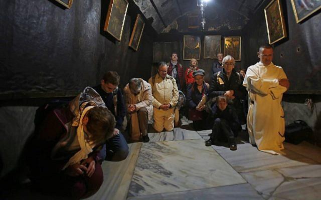 Des pèlerins chrétiens prient dans la Grotte de la Nativité, à Bethléem, le 24 décembre 2018. (Crédit : Musa Al SHAER / AFP)