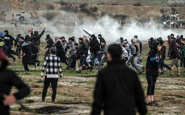 Des Palestiniens courent lors d'affrontements avec les forces israéliennes de l'autre côté de la barrière frontalière, à l'est de la ville de Gaza, le 28 décembre 2018. (Mahmud Hams/AFP)