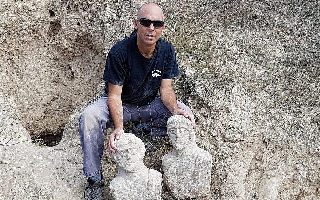 Nir Distelfeld, inspecteur de l'Unité de prévention des vols de l'Autorité israélienne des antiquités, avec les  deux bustes funéraires en calcaire qui ont été découverts après les fortes pluies du mois de décembre dans la région de Beit Shean par une randonneuse (Crédit : Eitan Klein, Autorité israélienne des antiquités)