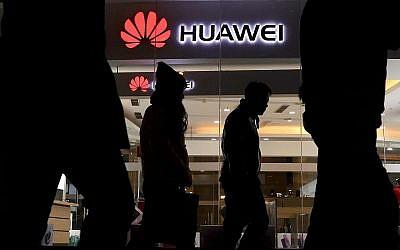 Des piétons passent devant un magasin de détail Huawei à Beijing le jeudi 6 décembre 2018. Jeudi, la Chine a exigé que le Canada libère un cadre de Huawei Technologies qui a été arrêté dans une affaire qui aggrave les tensions technologiques avec Washington et menace de compliquer les négociations commerciales. (AP Photo/Ng Han Guan)
