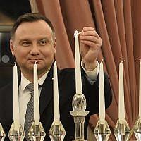 Le président polonais Andrzej Duda allume la dernière bougie pour Hanoukka au palais présidentiel de Varsovie, en Pologne, le 9 décembre 2018 (Crédit :  lAP Photo/Alik Keplicz)