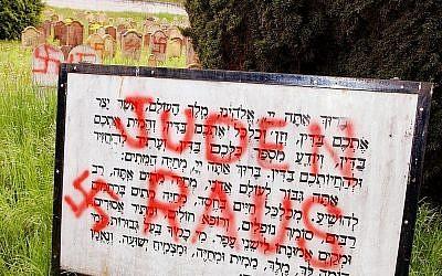 """Des inscriptions nazies disant """"Juifs dehors"""" et des croix gammées ont été peintes à l'entrée d'un cimetière juif à Herrlisheim, dans l'Est de la France, sur cette photo du 30 avril 2004. (AP Photo/Gil Michel)"""