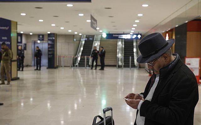 Un voyageur regarde son smartphone à l'aéroport d'Orly, au sud de Paris, le 18 mars 2017 (Crédit : AP Photo/Kamil Zihnioglu)