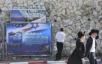 Les Juifs ultra-orthodoxes passent devant un panneau saluant le président américain Donald Trump avant sa visite à Jérusalem, le 19 mai 2017 (Crédit : AP Photo/Oded Balilty)